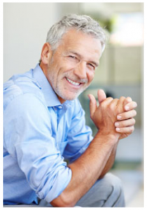 Older man sitting and smiling with hands together