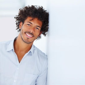 Man with curly hair smiling while leaning on wall