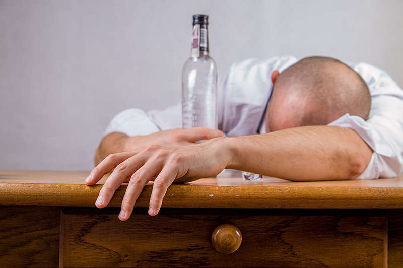Man passed out from his addiction to alcohol possibly passed on genetically.
