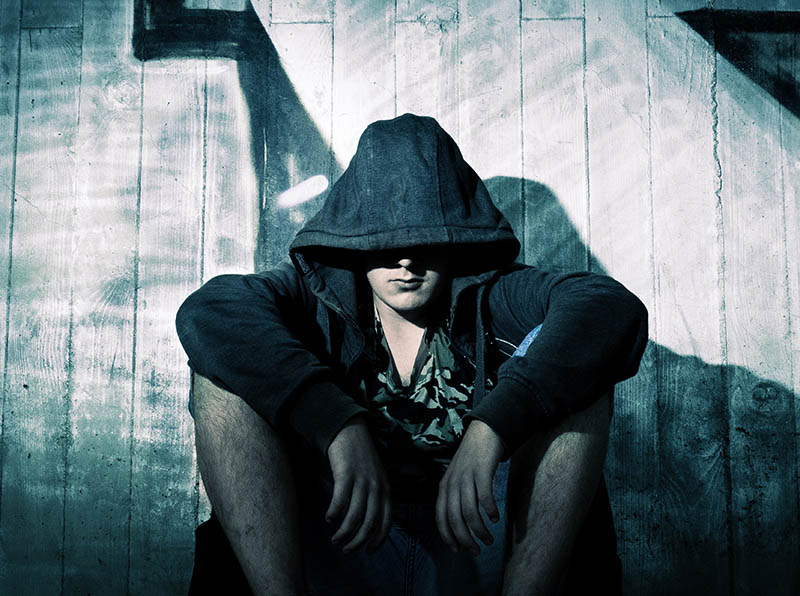 Man trying to beat addiction sitting sadly in a dark alley with a hoodie on